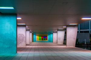 un tunnel en béton aux murs colorés par des lumières différentes