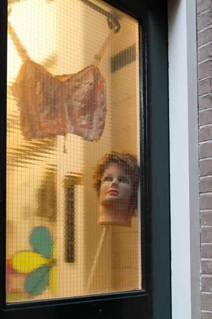 tête de mannequin sur un manche avec un corset derrière une fenêtre
