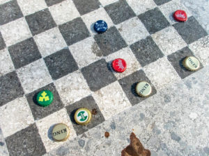 des capsules de bière servent de pions à un jeu d'échec de rue