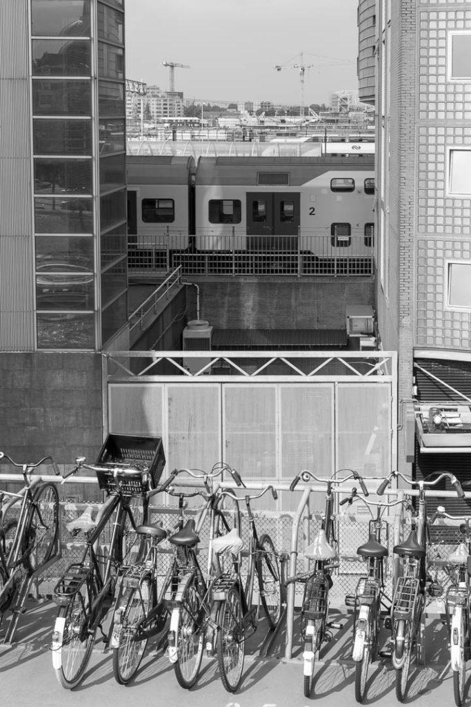 rangée de vélos avec train entre 2 bâtiments