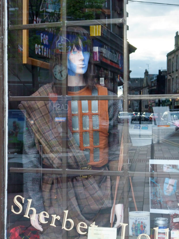 mannequin Highlander dans une vitrine qui reflète la ville de Stirling