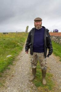 un Ecossais pose devant chez lui avec un menhir