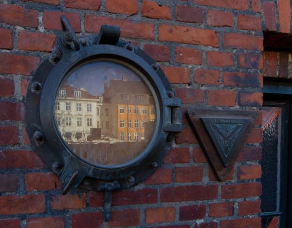 hublot sur le mur d'un bâtiment qui reflette les maisons colorées du port de Nyhavn