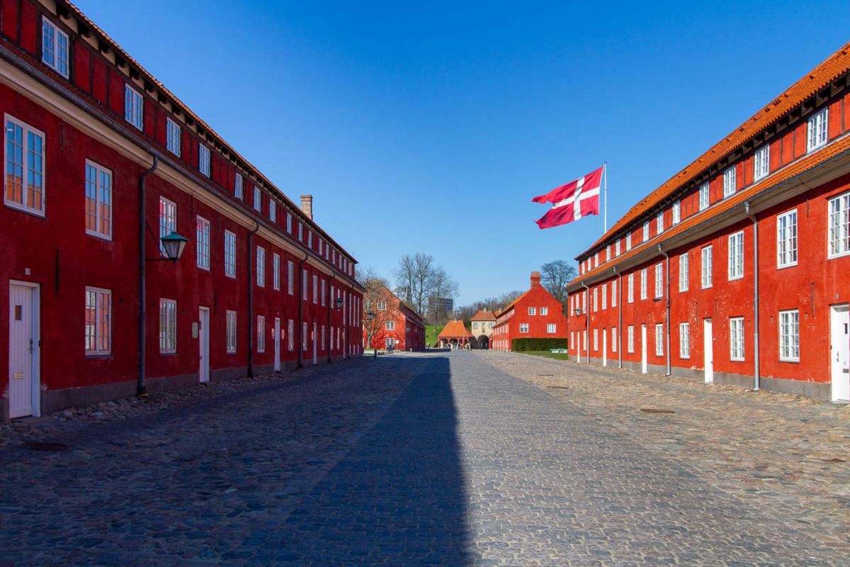 bâtiments de caserne rouge vifs avec le drapeau du Danemark qui flotte sur un ciel bleu