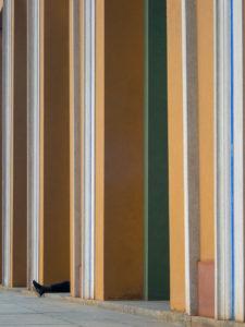 des pieds dépassent d'un mur aux couleurs verticales