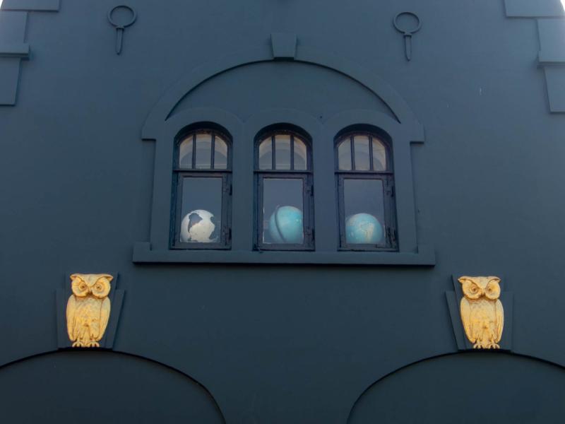 bas-relief hiboux dorés sur un mur foncé avec un globe terrestre derrière chaque fenêtre