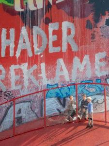 enfants au pied d'un immense mur peint