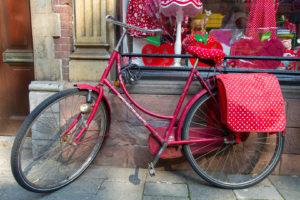 un vélo rouge à pois blancs garé sur une vitrine qui vend des objets rouges à pois blancs