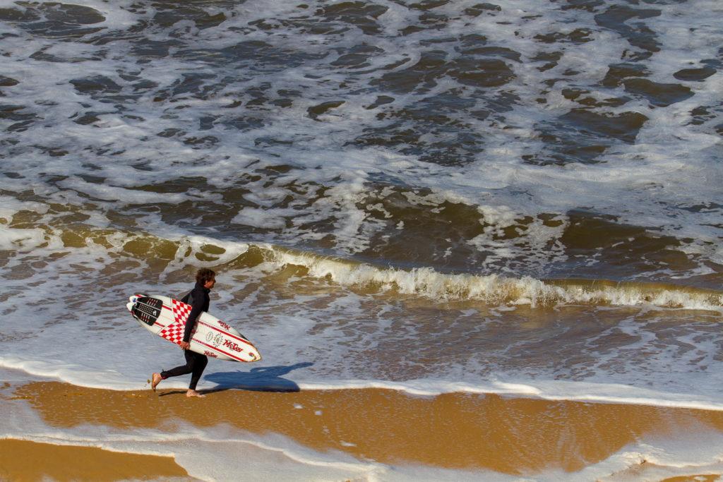surfeur qui se dirige vers la mer planche sous le bras